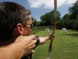 Guests staying at this party house, enjoying some archery in the garden of Tone Dale House
