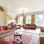 The large and comfortable sitting room at Tone Dale House, with open fire and large windows looking towards the gardens