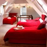 This attic bedroom is ideal for large family gatherings, with 4 single beds for children at Cotswold Manor