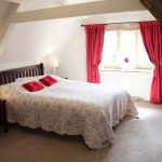 Cosy bedroom tucked in the eaves of Cotswold Manor, part of The Big House Company
