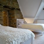 A twin room at Cotswold Manor that has a feature wall of exposed stone