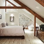A free standing bath, roll top bed and exposed beams in this large and attractive bedroom at Devon Farmhouse