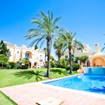 Palm trees and an outdoor pool in the grounds of Marbella Villa, available through The Big House Company