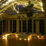 The Orangery is a charming space for a special celebration dinner party with fairy lights and candles glowing
