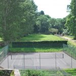 Our party house in Somerset has a tennis court next to the long tree lined driveway.