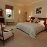 Bedroom 1 has a king size antique bed, elegant furniture and views over the garden.