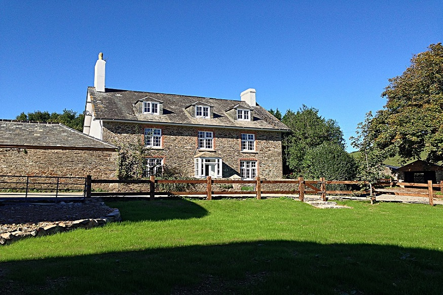 Devon Farmhouse pictured from the sweeping driveway, overlooking fields and glorious countryside