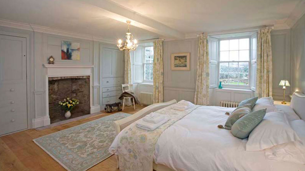 This charming bedroom at Berry House is decorated in soft pastels and has large windows overlooking the garden