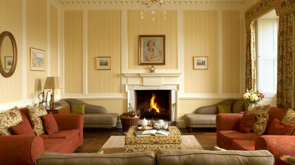 The large, elegant sitting room at Berry House has a roaring log fire and plenty of comfortable seating for large groups.