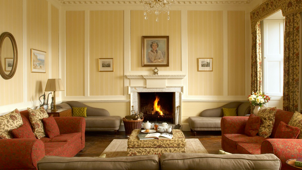 The large, elegant sitting room at Berry House has a roaring log fire and plenty of comfortable seating for large groups