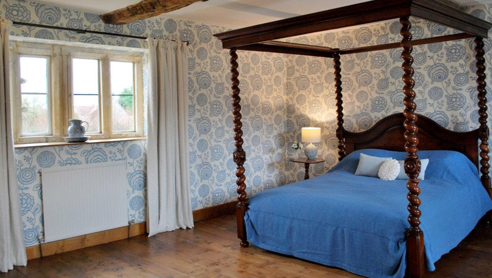 A romantic four poster bed in this stylish room at our Cotswold Mansion for rent.