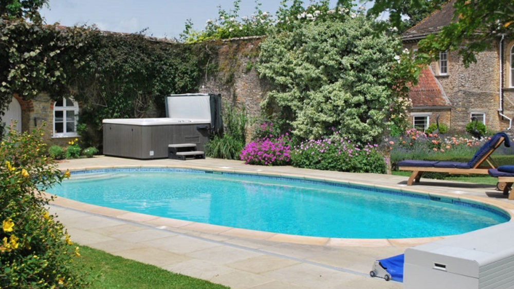 This big holiday house in Somerset has an outdoor pool, hot tub and large, colourful gardens.