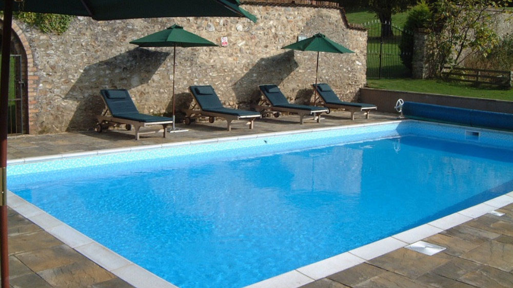 The large outdoor heated pool is in the sheltered, walled garden and has sun loungers and sun umbrellas