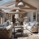 The contemporary designed sitting area, with pale oak exposed beams and large sofas at Midlands Villa