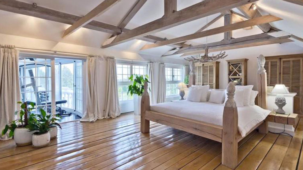 The master bedroom at Midlands Villa has a wall of windows, beautiful beams and a large bed as the centre piece of the bedroom