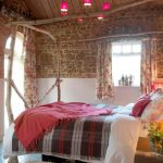 Bedroom 8 has exposed brickwork to create a warm, rustic feel at this party house.