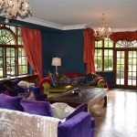 The large living room at this big house to hire has sumptuous furnishings and large windows looking out to the garden