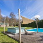 The heated outdoor pool in the garden at Sussex Manor with sun loungers.