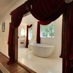 An enormous bathroom with velvet curtains.