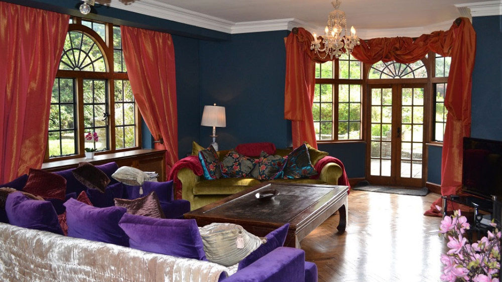 The sitting room has sumptuous furnishings and views over the garden from the large windows