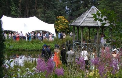 The lakeside wedding pergola at Widcombe Grange with wedding guests watching the wedding ceremony.