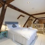 Bedroom 7 is a charming, cosy bedroom in the eaves, with wooden beams, painted floorboards and rugs