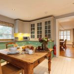A scrubbed pine table and country style kitchen at Dorset Lodge