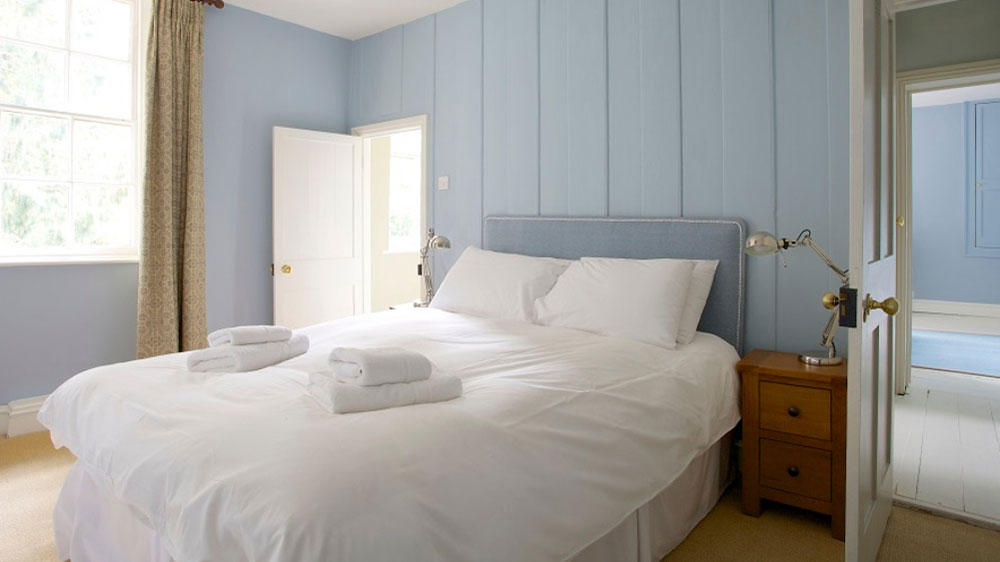 Delightful double bedroom with pale blue paintwork at this big house.