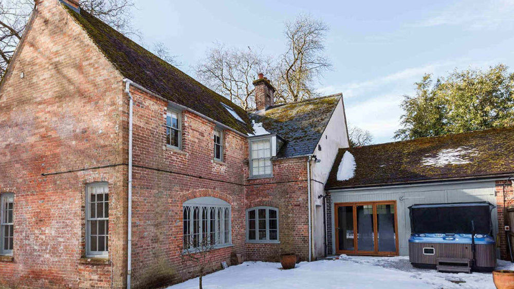 The exterior of our big house in Dorset with snow on the ground.