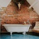This bathroom has a roll top bath and attractive exposed brickwork.