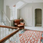 The hallway and stairs, rugs and chair.