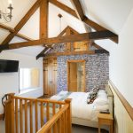 Exposed beams give this bedroom a cosy atmosphere at Tatham House in Somerset