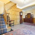The oak paneled hall with stairs leading to 8 of the 10 bedrooms at Tatham House in Somerset