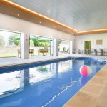 The indoor pool at Tatham House has bi-fold doors opening onto the walled garden and terrace area