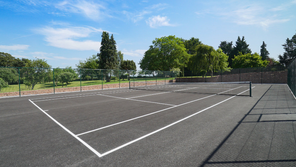 The tennis court at Tatham House is nestled beside the walled garden, overlooking the Quantocks