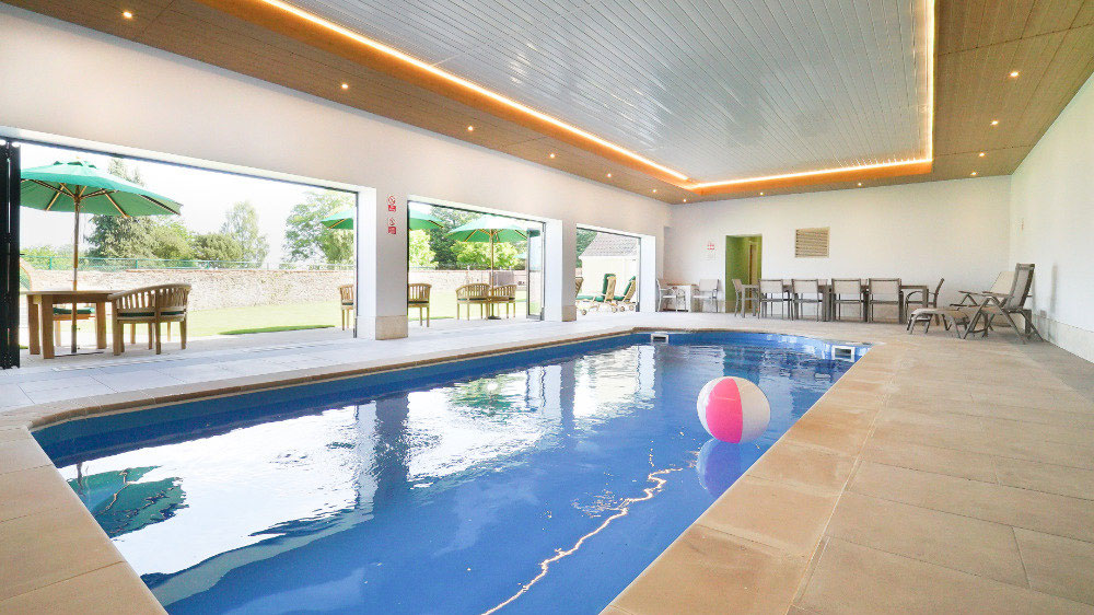 The indoor pool at Tatham House, Somerset with bi-fold doors out to the walled garden, terraces & seating