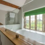 The large sunken bath has views over the garden at our party house in Somerset