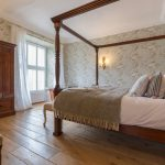This bedroom has a romantic four poster bed and beautiful wooden floors.