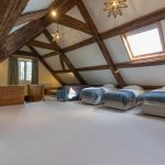 With exposed beams, this attic bedroom has 3 single beds.