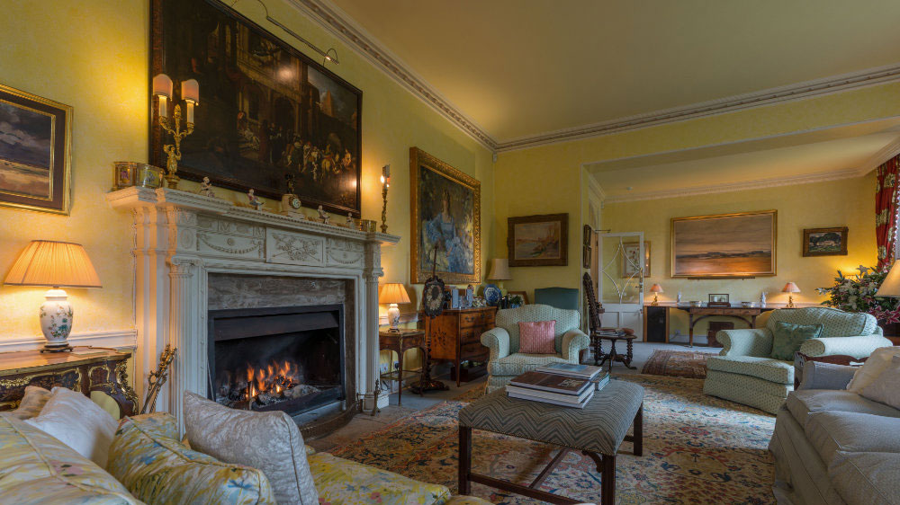 Large sitting room with a roaring open fire at Ilminster Manor