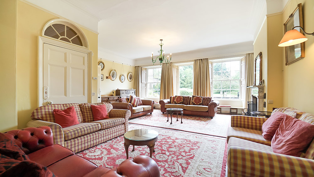The living room at Tone Dale House, Somerset, has plenty of sofas, an open log fire and large sash windows