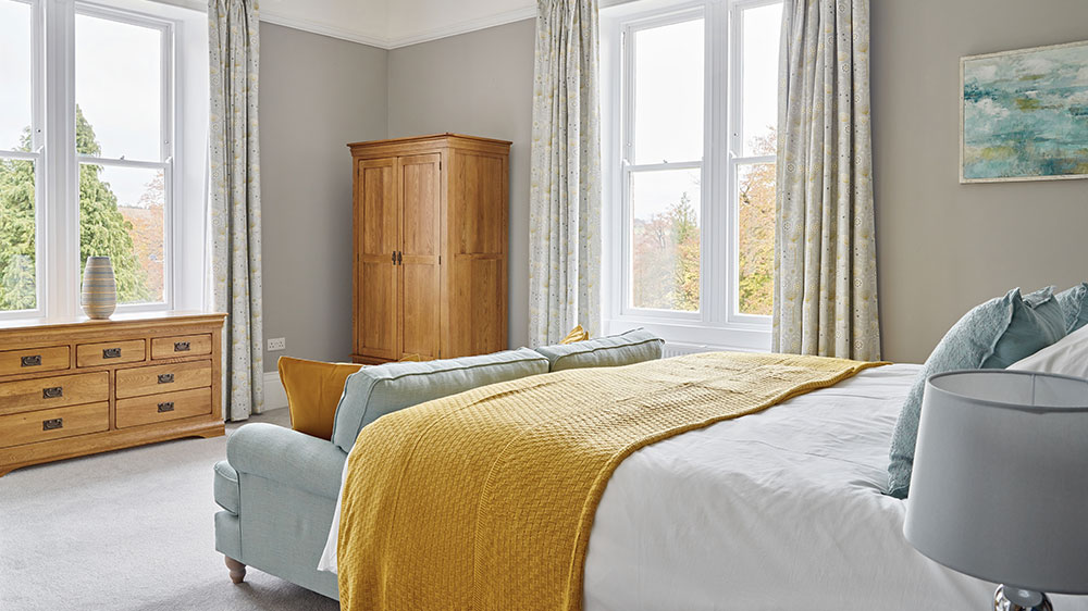 This bedroom is spacious with elegant windows and a large comfortable bed.