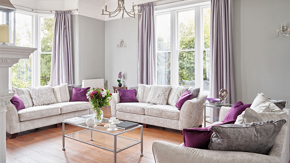 The large seating room has comfortable sofas and elegant large windows.