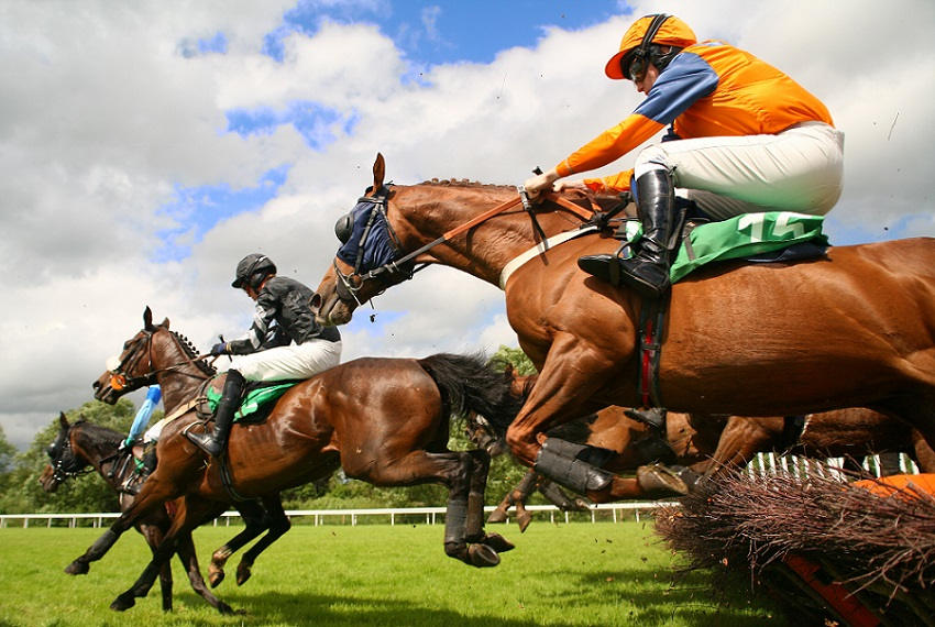 Race horses jumping over fences