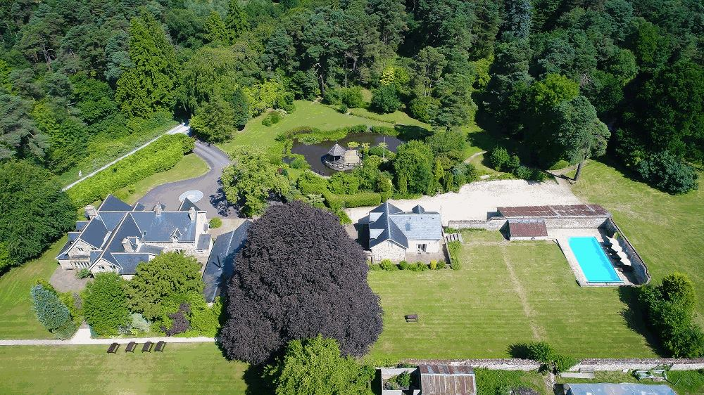 Aerial view of this big house in Somerset with outdoor pool and spacious grounds.